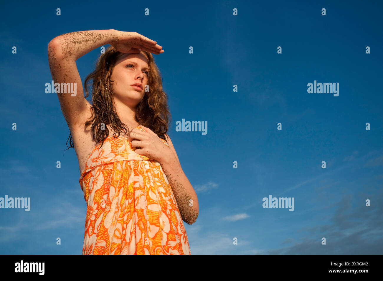 Young woman on beach looking into the distance - Stock Image
