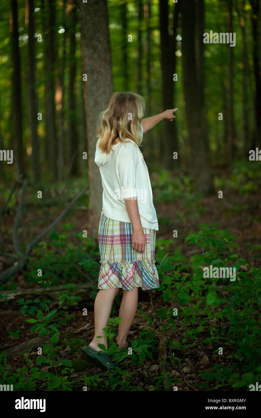 Young woman in woods pointing her finger into the distance - Stock Image