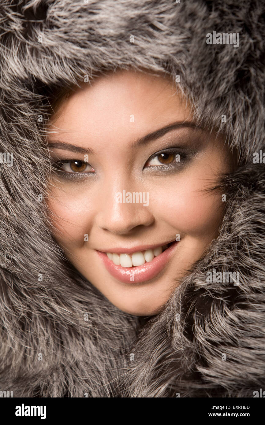 Close-up of young beautiful girl wearing fur-cap and smiling - Stock Image