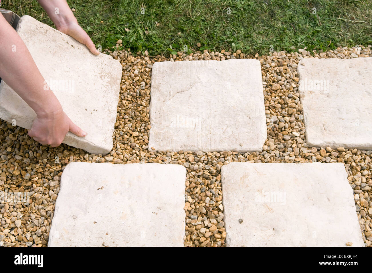 Hand positioning paving slabs on ground Stock Photo