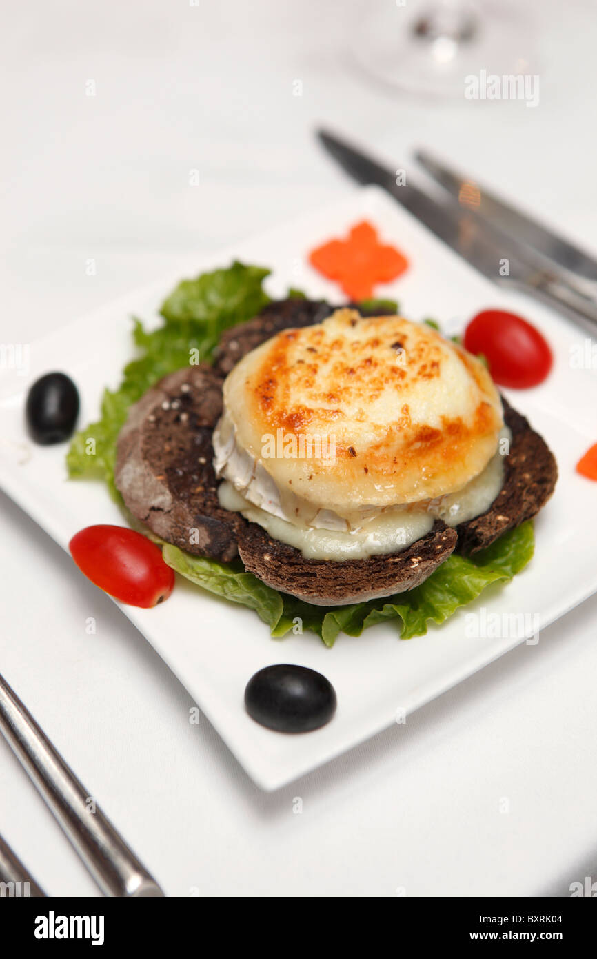 Gratinated goat's cheese with olive oil & honey served on toast served in a restaurant on Taipa, Macau - Stock Image