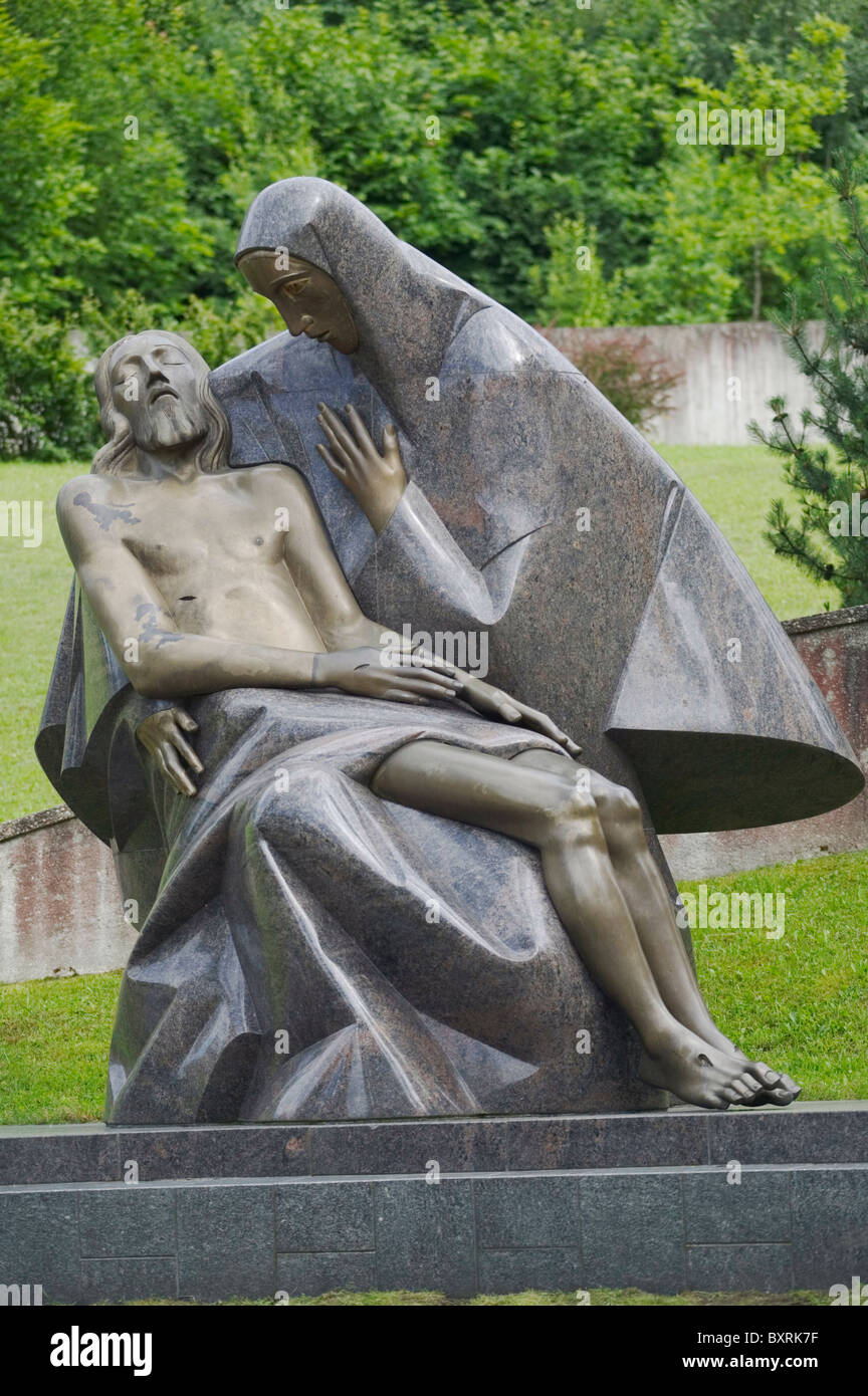 Lithuania, Vilnius, Antakalnis Cemetery, statue of Mary with crucified Jesus, at the graves of people killed by Stock Photo