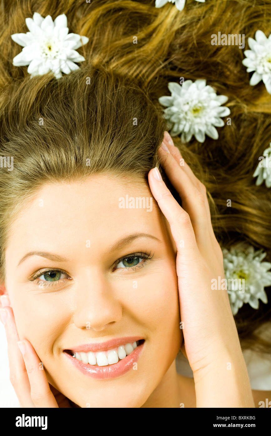 Photo of female's happy face being touched by her hands looking at camera - Stock Image