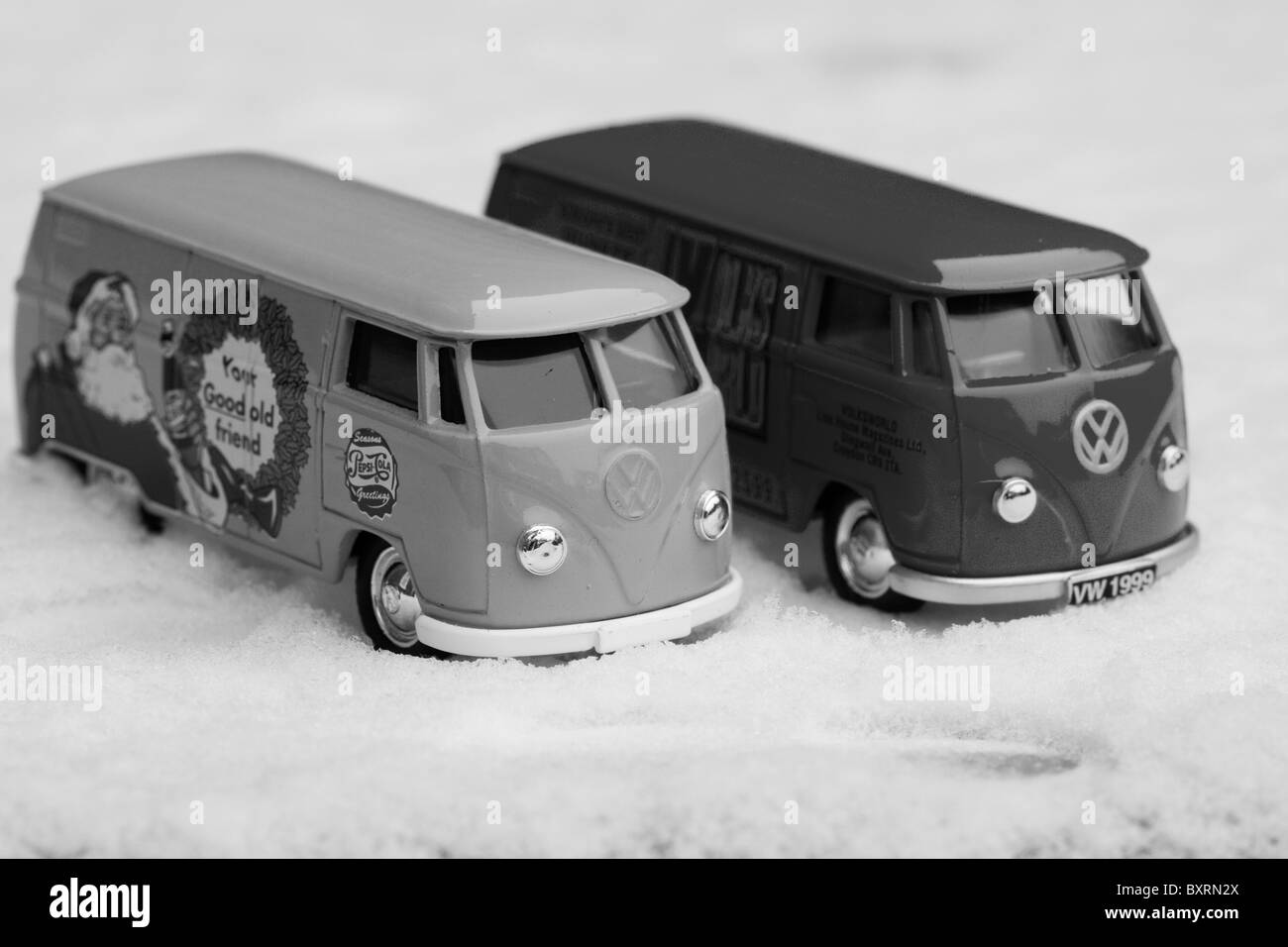 Children's collectible toy models of  Volkswagen split screen panel vans on Snow Black and White - Stock Image