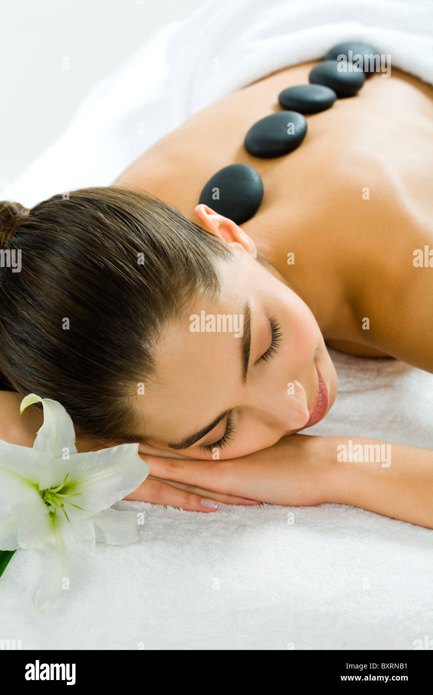 Image of a pretty girl lying in the beauty salon with closed eyes and enjoying spa procedure with madonna lily by - Stock Image