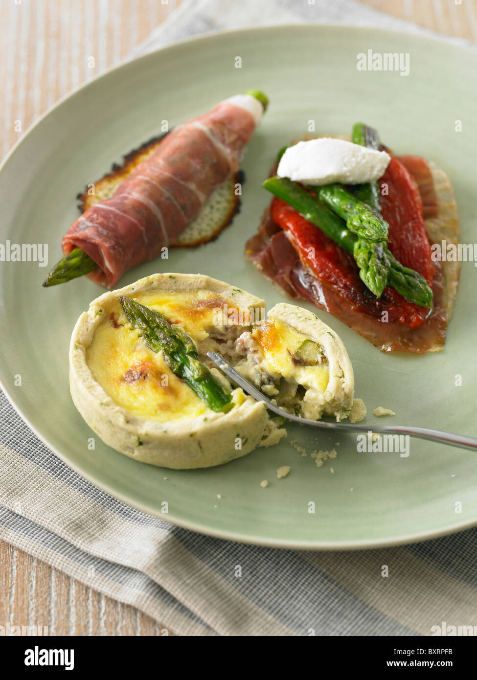 Trio of starters on plate, asparagus wrapped in smoked parma ham, asparagus tart, and parma ham with red peppers - Stock Image