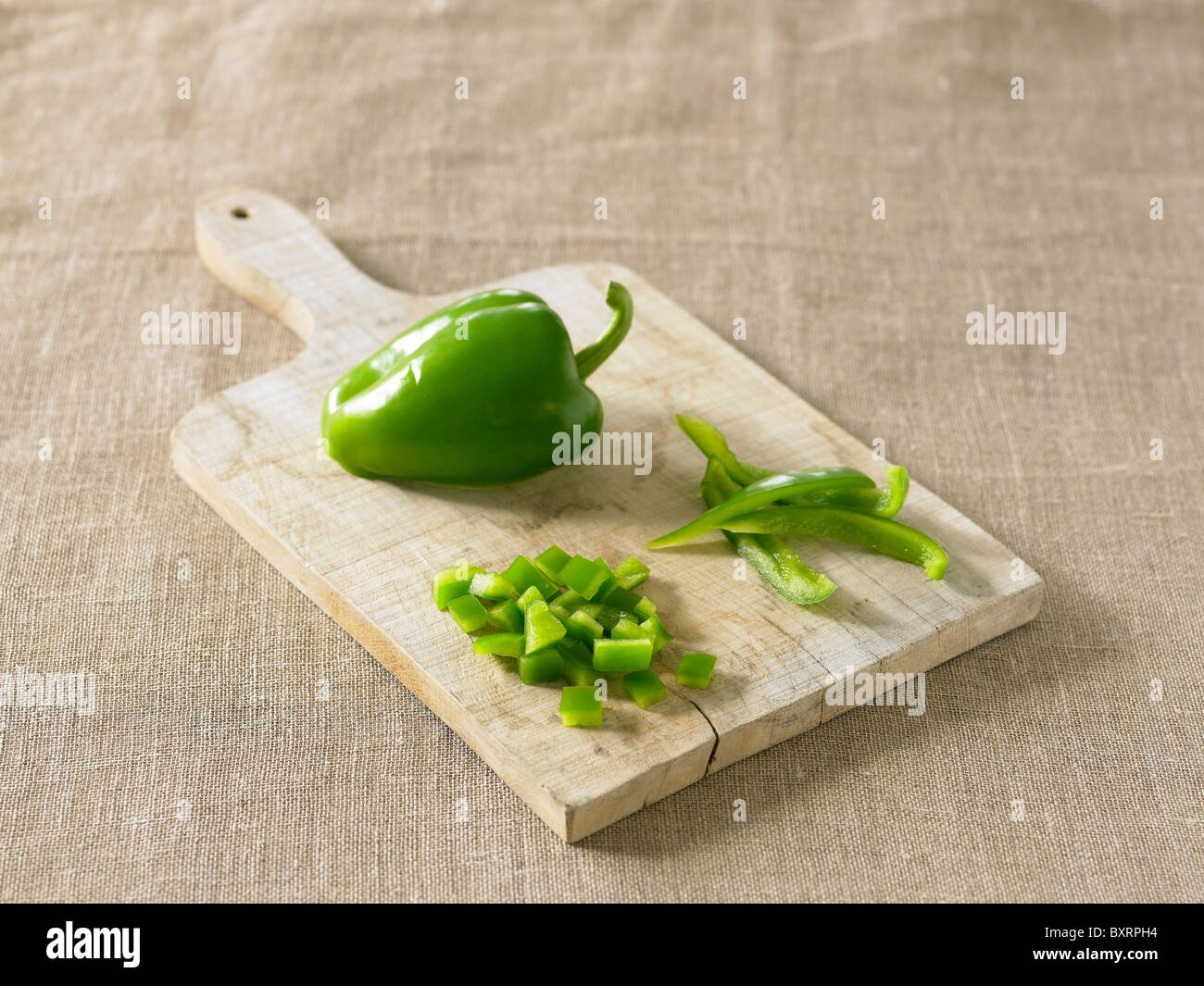 Green pepper on chopping board, chopped and sliced - Stock Image