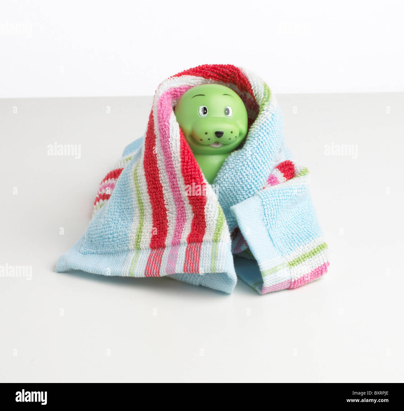 Plastic green toy wrapped in towel - Stock Image