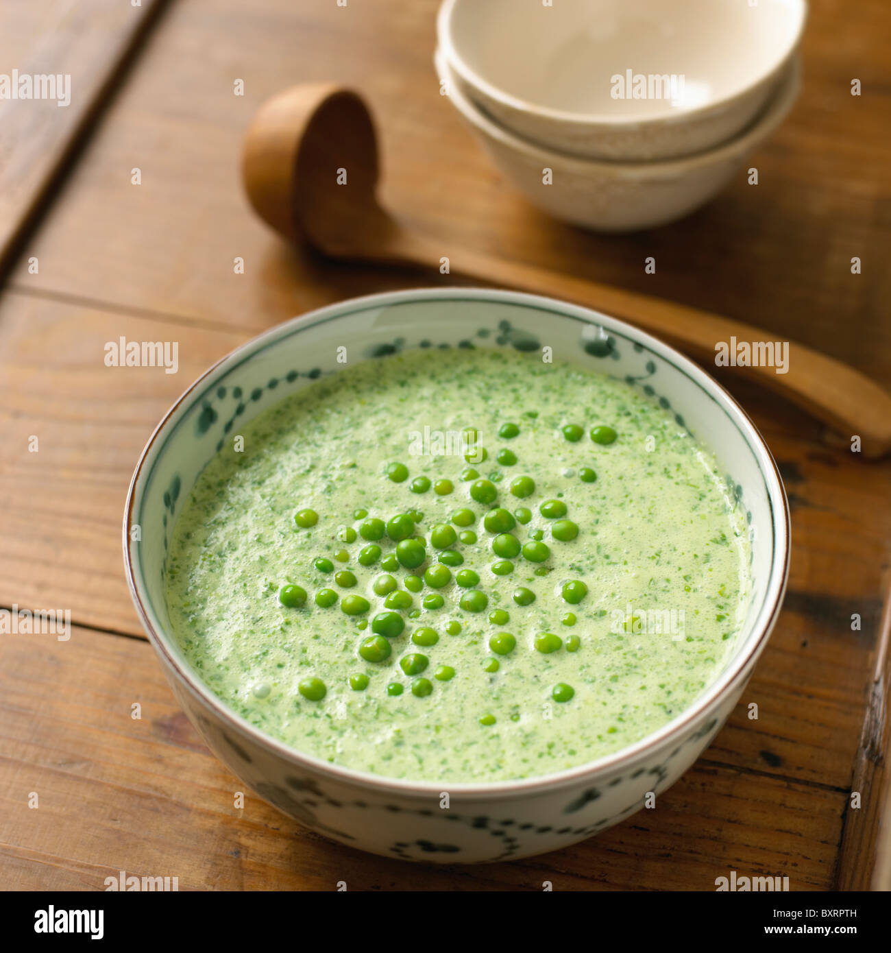 Chilled lettuce soup in a bowl with peas on top - Stock Image
