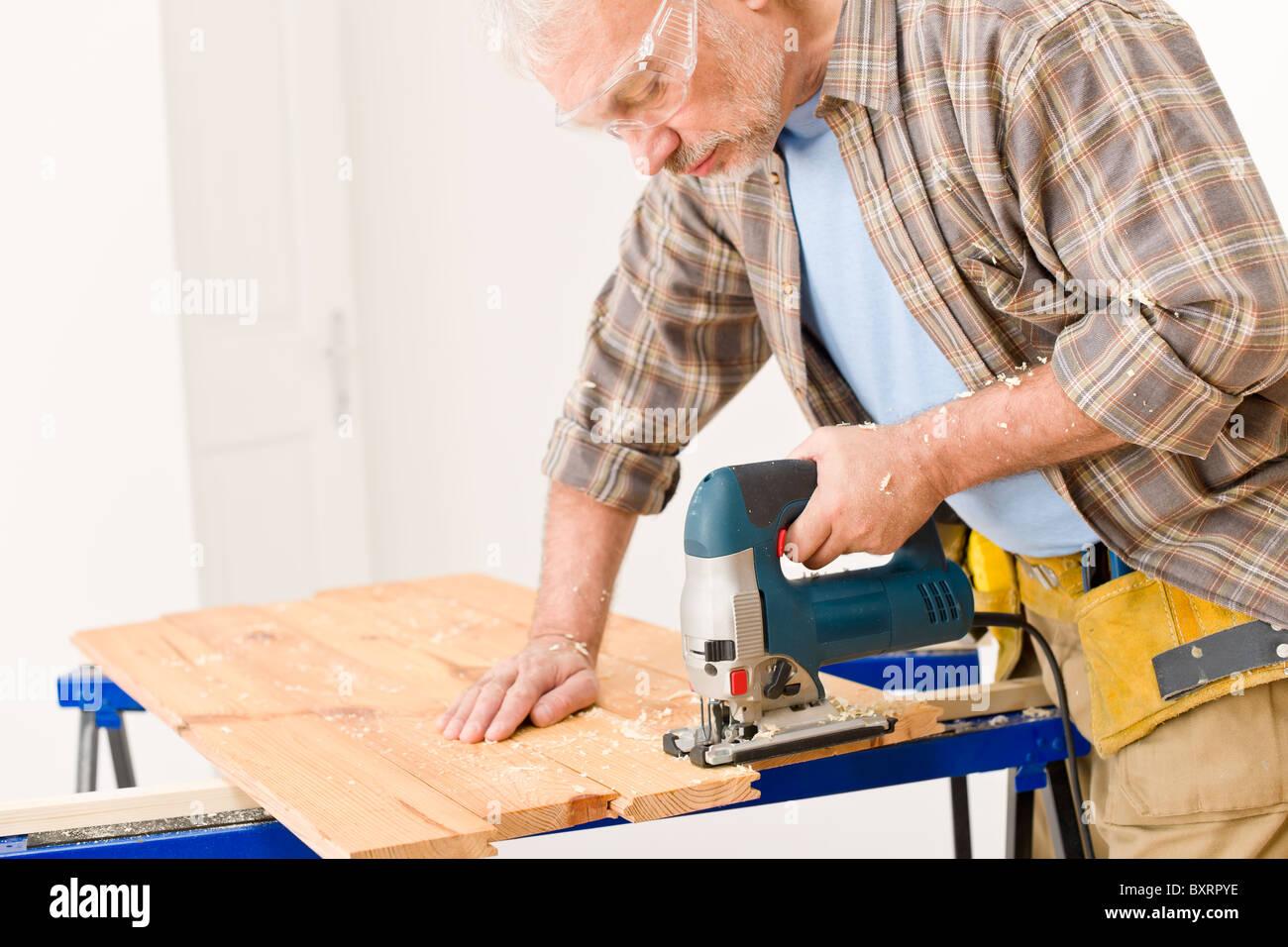 Home improvement - handyman cut wood with jigsaw in workshop Stock Photo