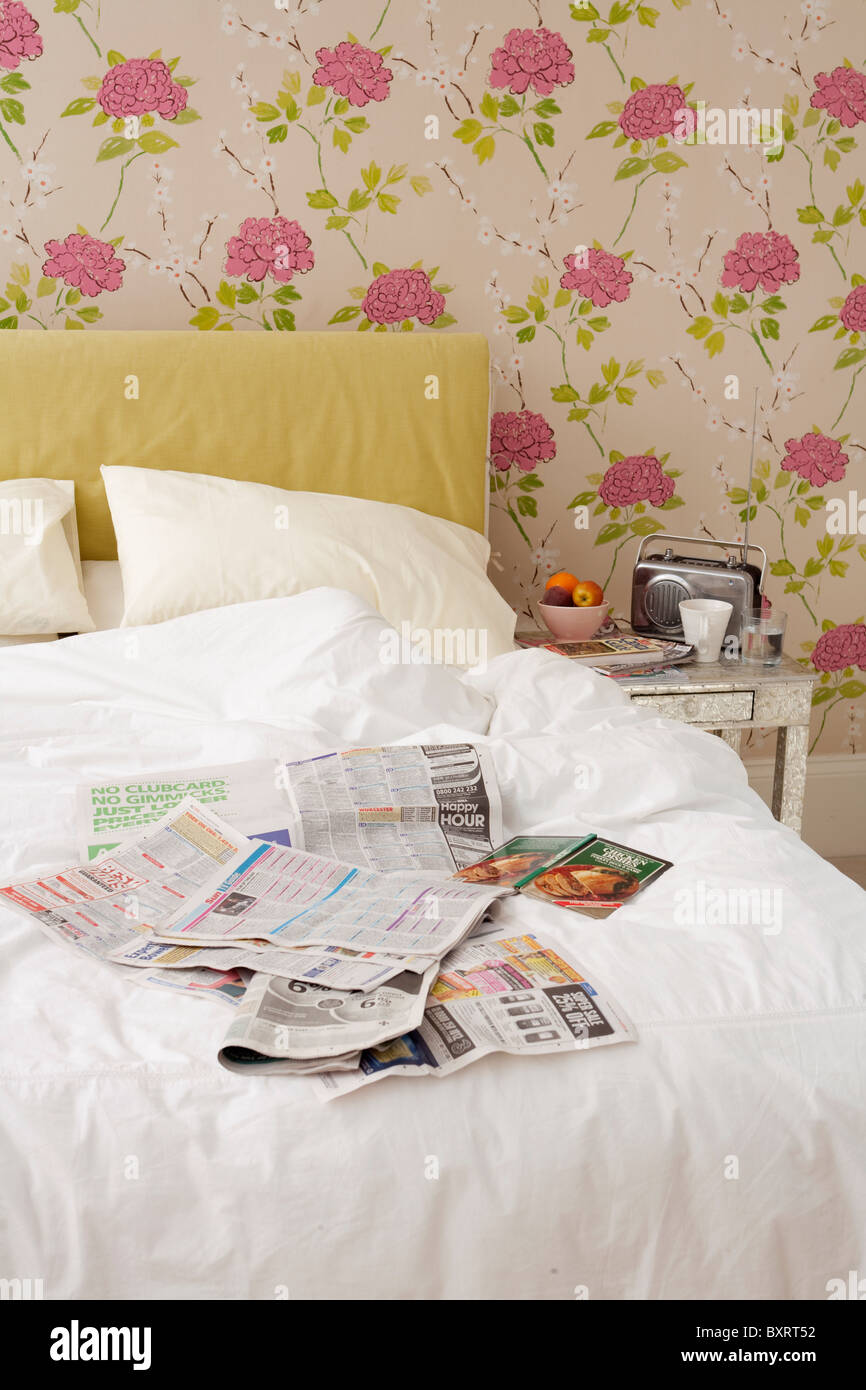 Messy bed with covered in newspapers - Stock Image
