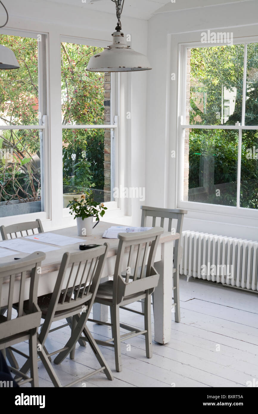 Simple white dining room with table and chairs by windows - Stock Image