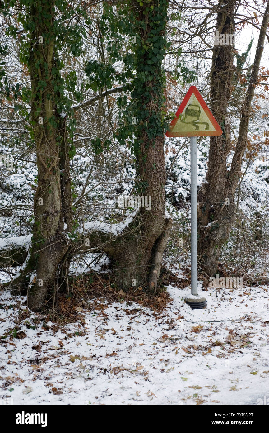 sign next to ice covered road warning of slippery surface - Stock Image