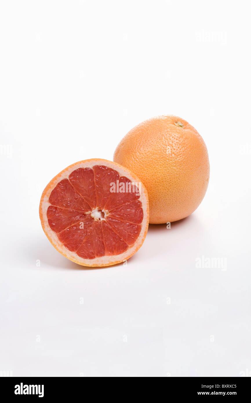Whole and halved pink grapefruit on white background - Stock Image