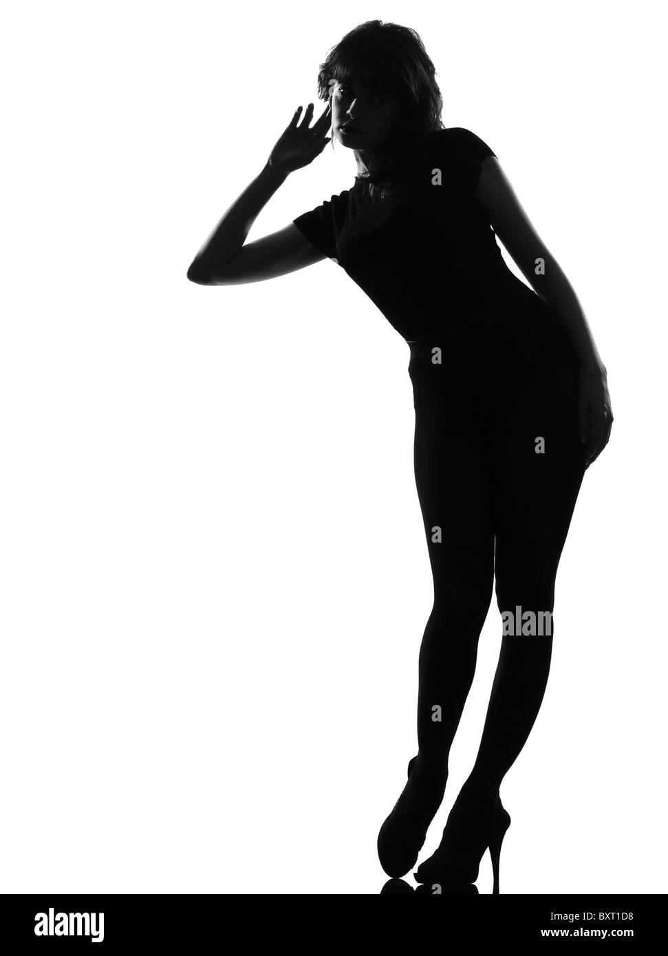 full length silhouette in shadow of a young curious listening woman in studio on white background isolated - Stock Image