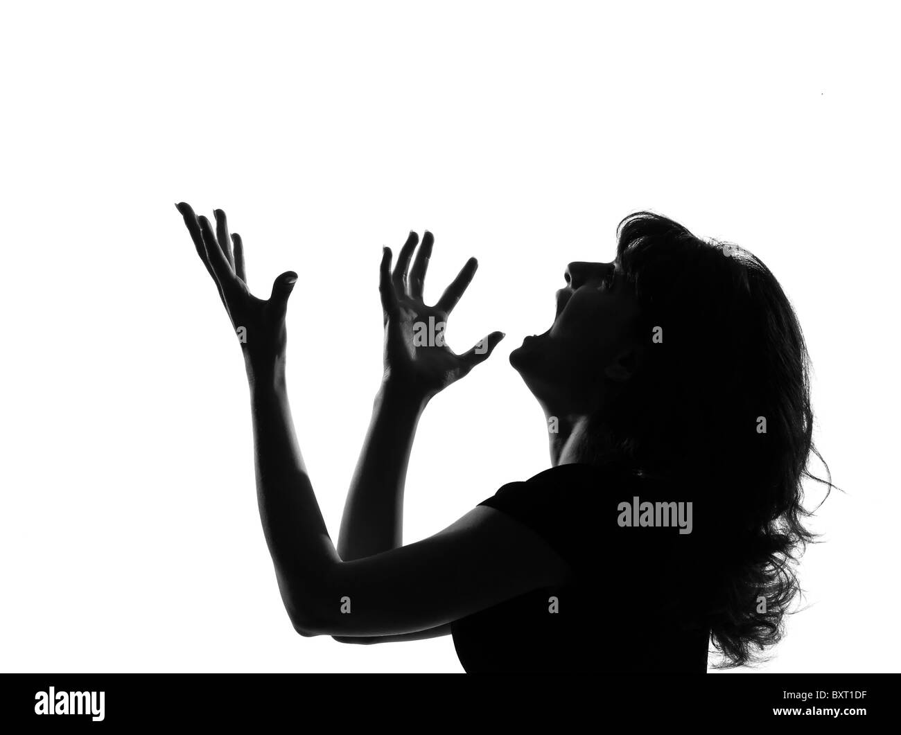 portrait silhouette in shadow of a young woman screaming anger  in studio on white background isolated - Stock Image