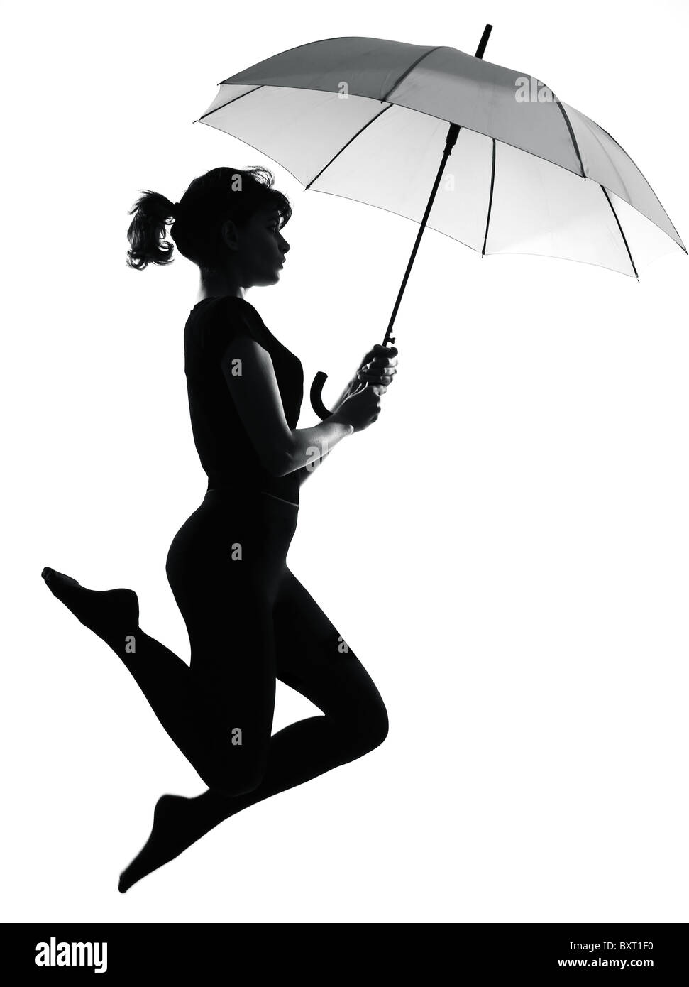full length silhouette in shadow of a young woman flying with open umbrella  in studio on white background isolated - Stock Image