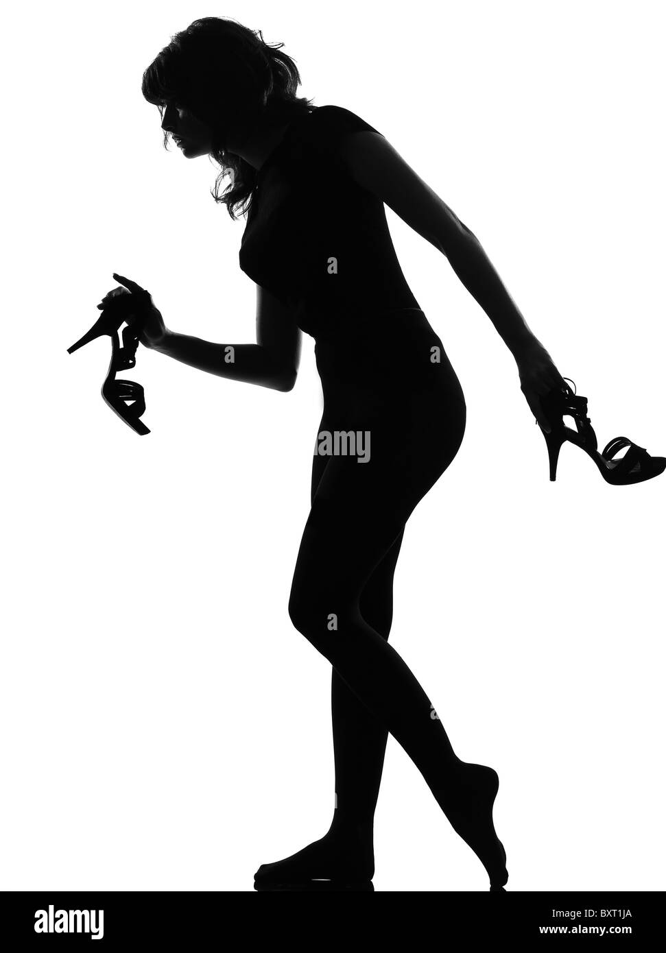 silhouette in shadow of a young woman walking quite    barefoot on  tiptoe holding high heel shoes in studio on - Stock Image