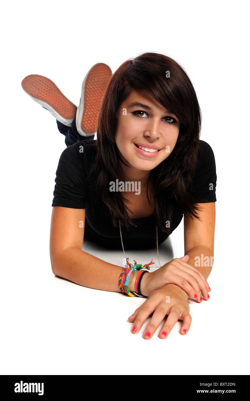 Portrait of Hispanic teen laying on floor isolated over white background - Stock Image