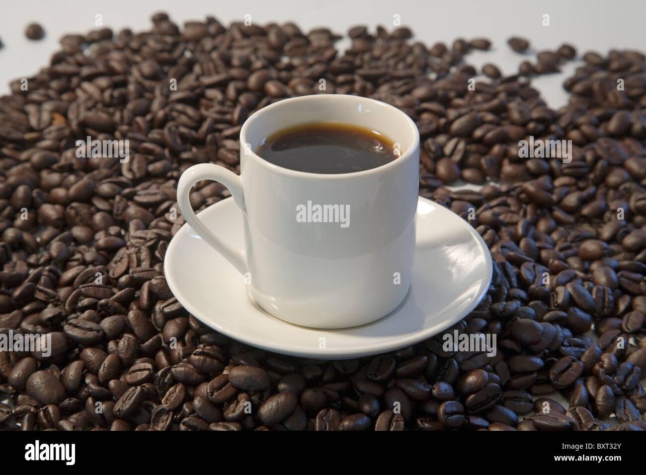 A cup of espresso with dark roast espresso beans - Stock Image