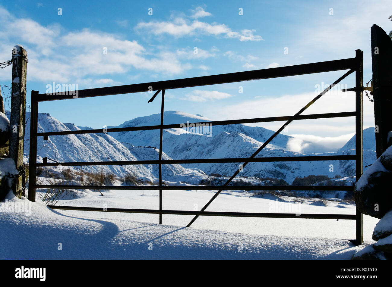 The Snowdon massif in winter, seen through a barred gate. Stock Photo