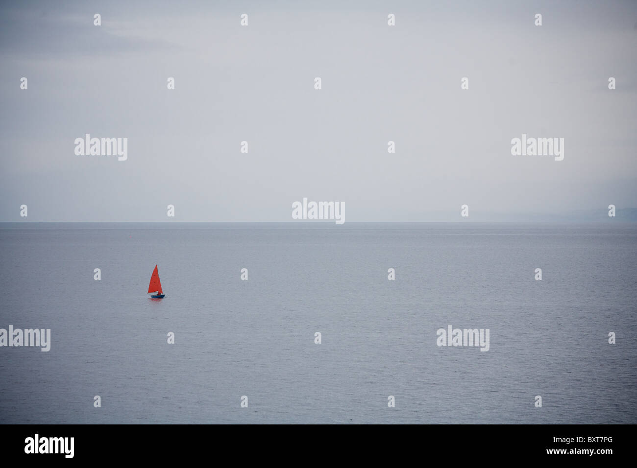 Sailing boat with red sail, sailing off the coast at Big Sand, Gairloch. - Stock Image