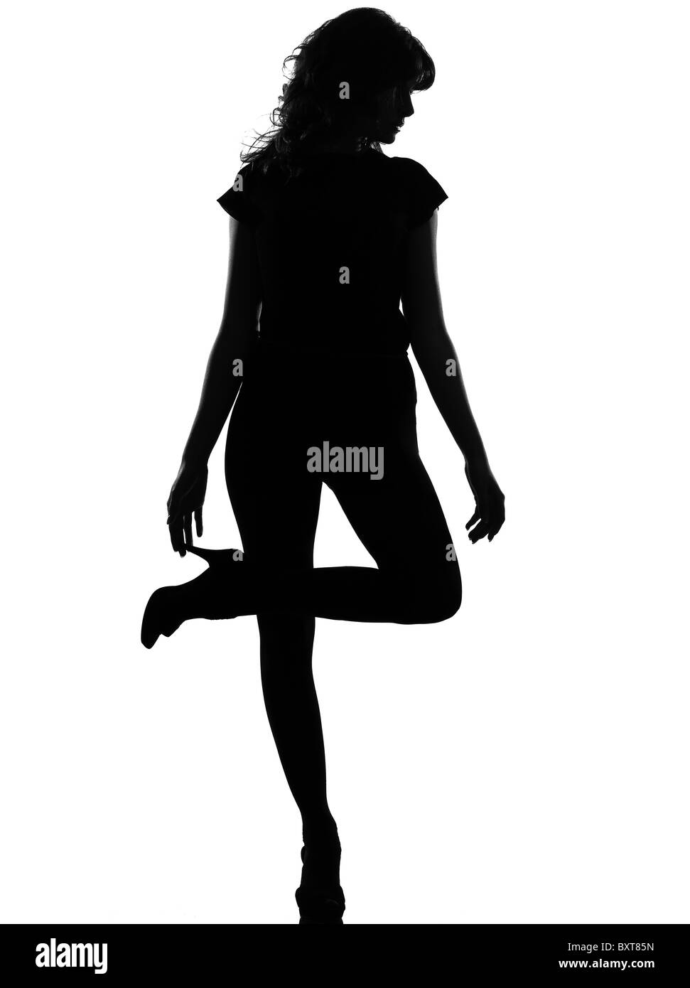 full length silhouette in shadow of a young woman standing on one leg thinking in studio on white background isolated - Stock Image