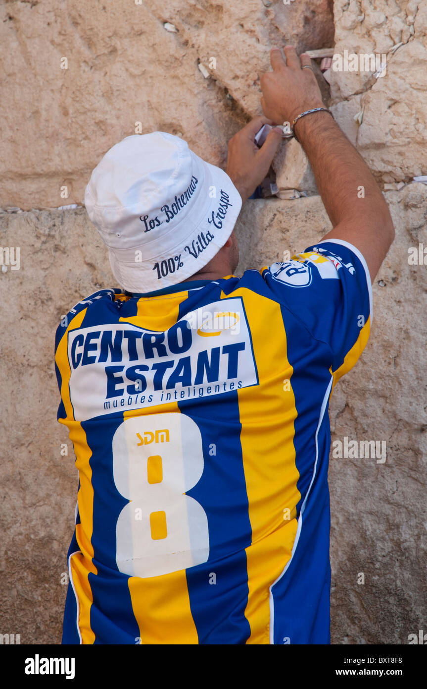 Western Wall. Man placing a paper note in a crack at wall. Jerusalem Old City - Stock Image