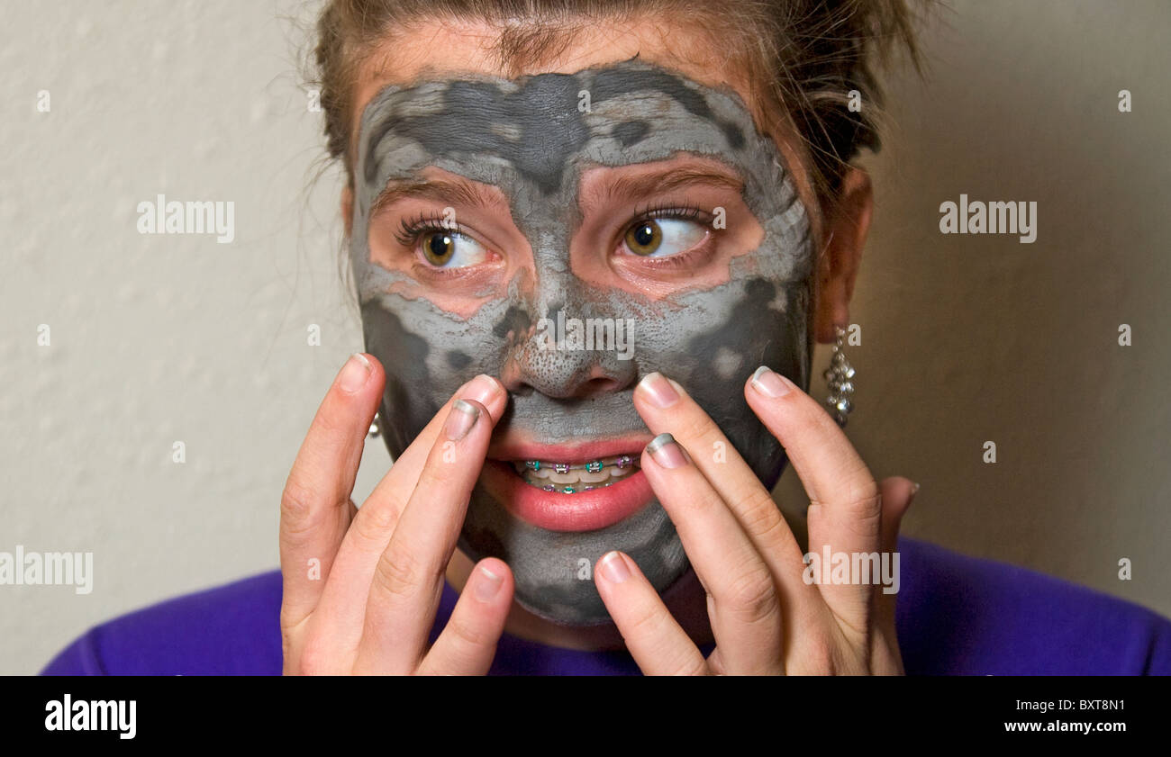 A teenage girl wearing braces on her teeth and a facial beauty mask prepares for a date - Stock Image