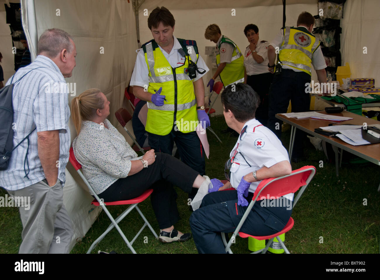 AMBULANCE STAFF  COMFORTING THE  UNWELL  PERSON IN THE TENT - Stock Image