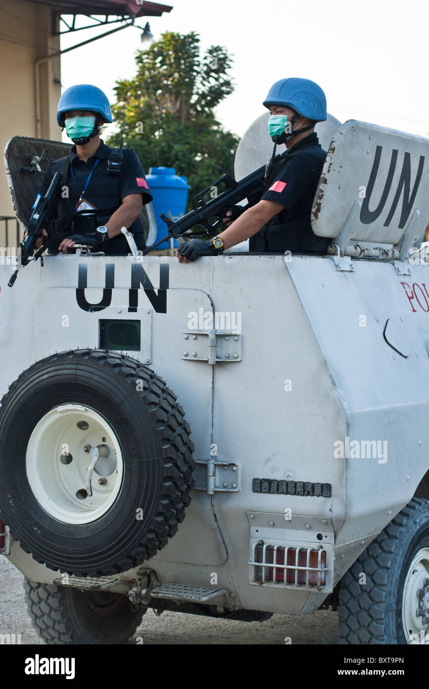 A United Nations vehicle and soldiers provide protection to a humanitarian aid agency distributing food in Haiti. - Stock Image
