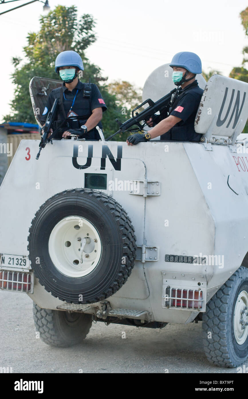 A United Nations vehicle and soldiers provide protection to a humanitarian aid agency distributing food in Haiti. Stock Photo