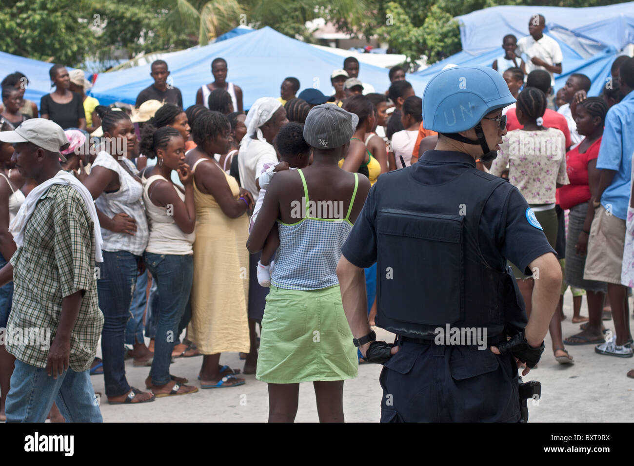 Haitians queue up in preparation for a massive food distribution to 300,000 people after their city was leveled - Stock Image