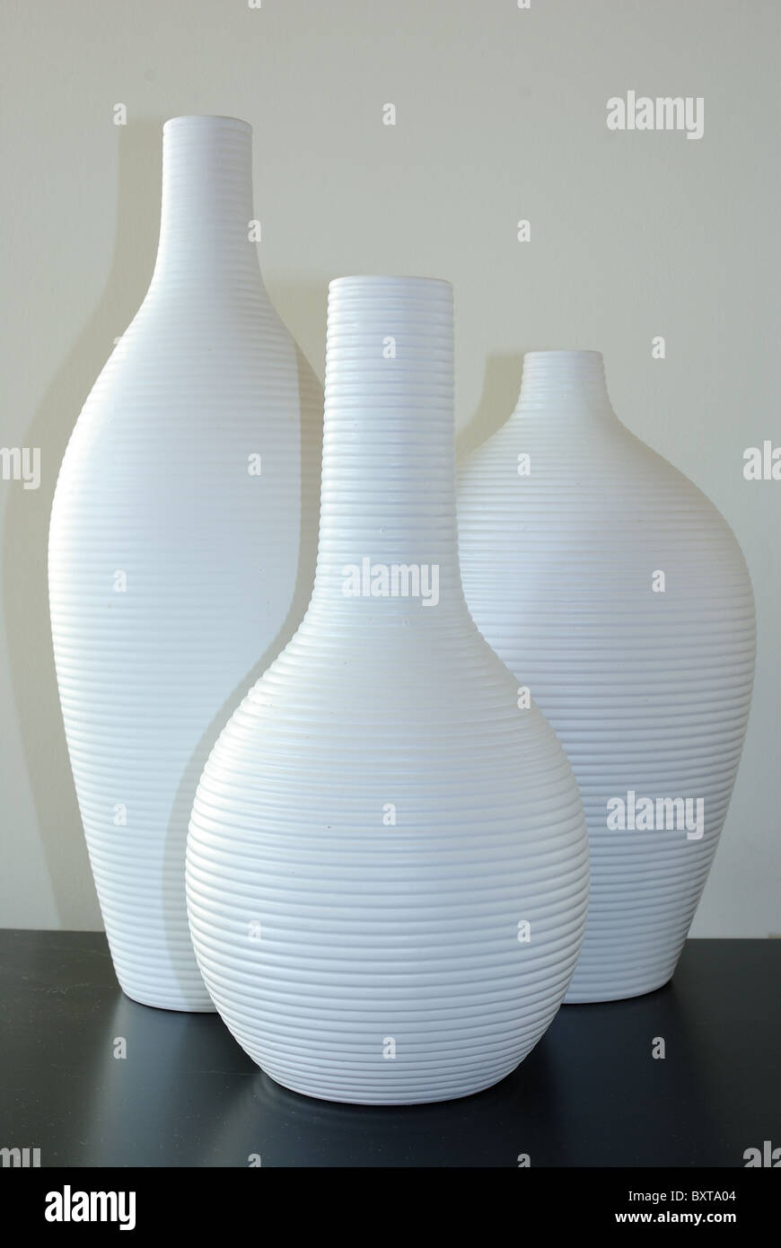 White Vases on a black countertop - Stock Image