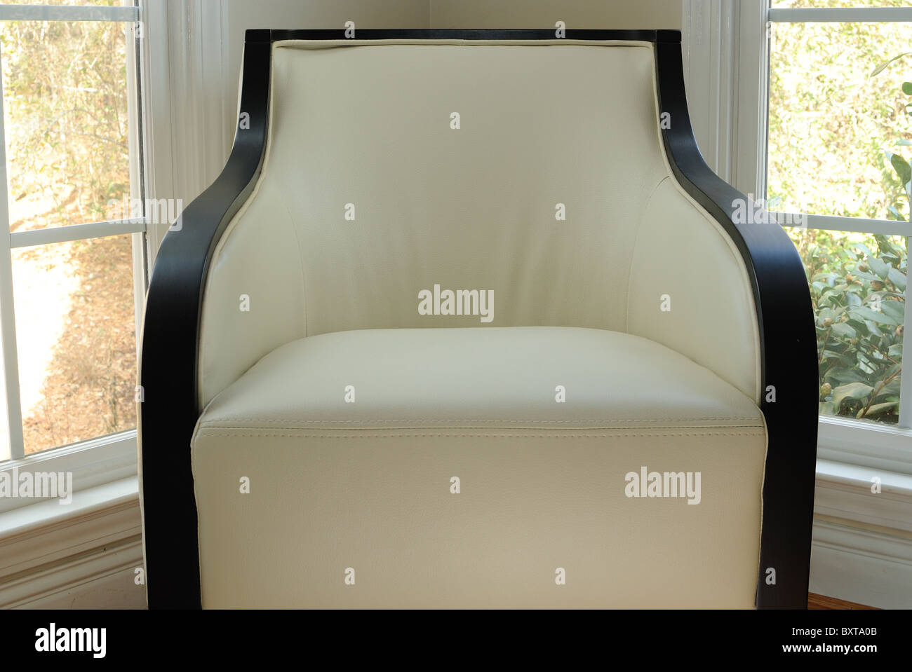 Modern white chair in a window corner - Stock Image