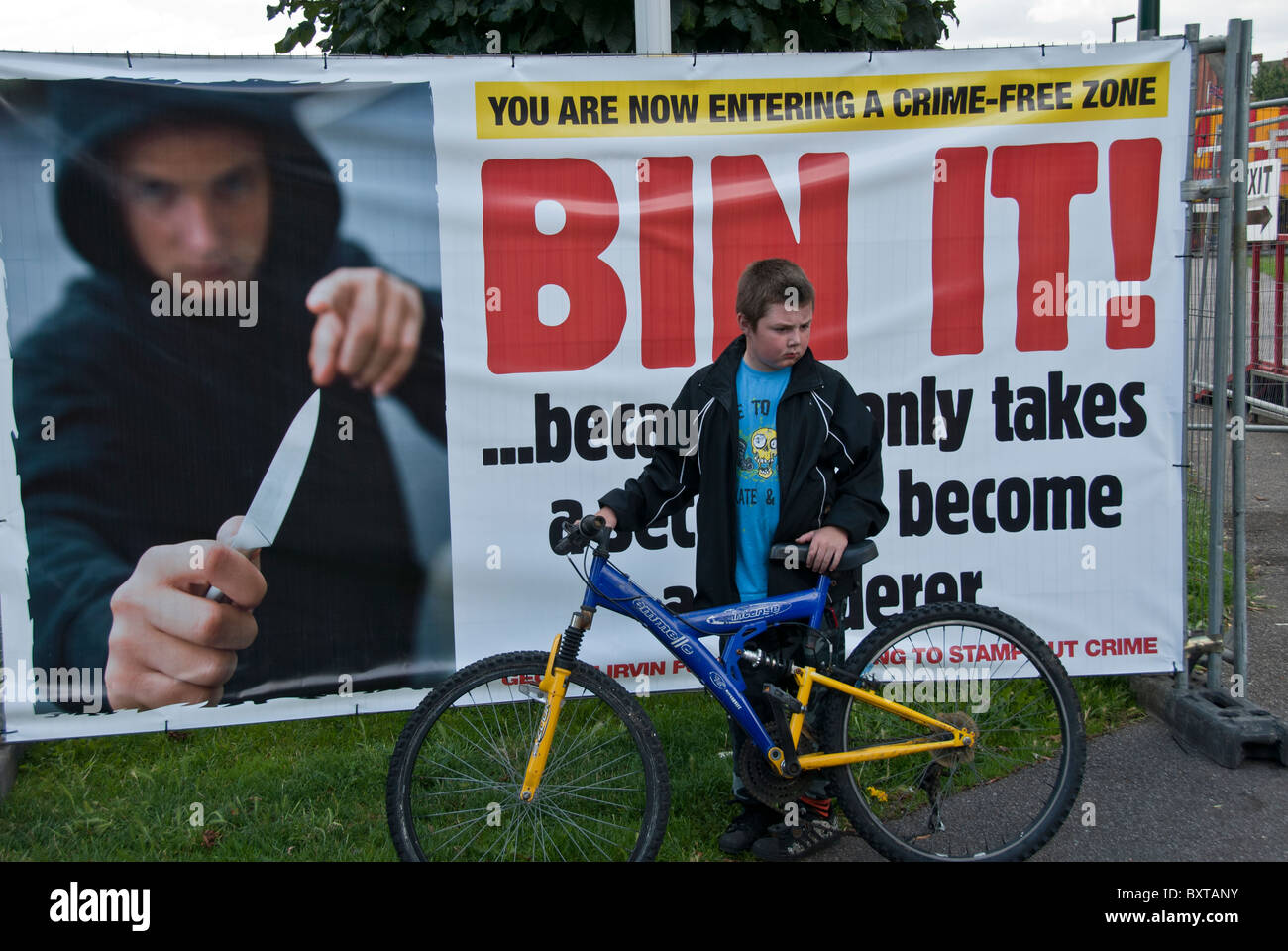 YOUNG BOY HOLDING HIS BIKE IN FRONT OF ANTI KNIFE CRIME ADD PANE - Stock Image