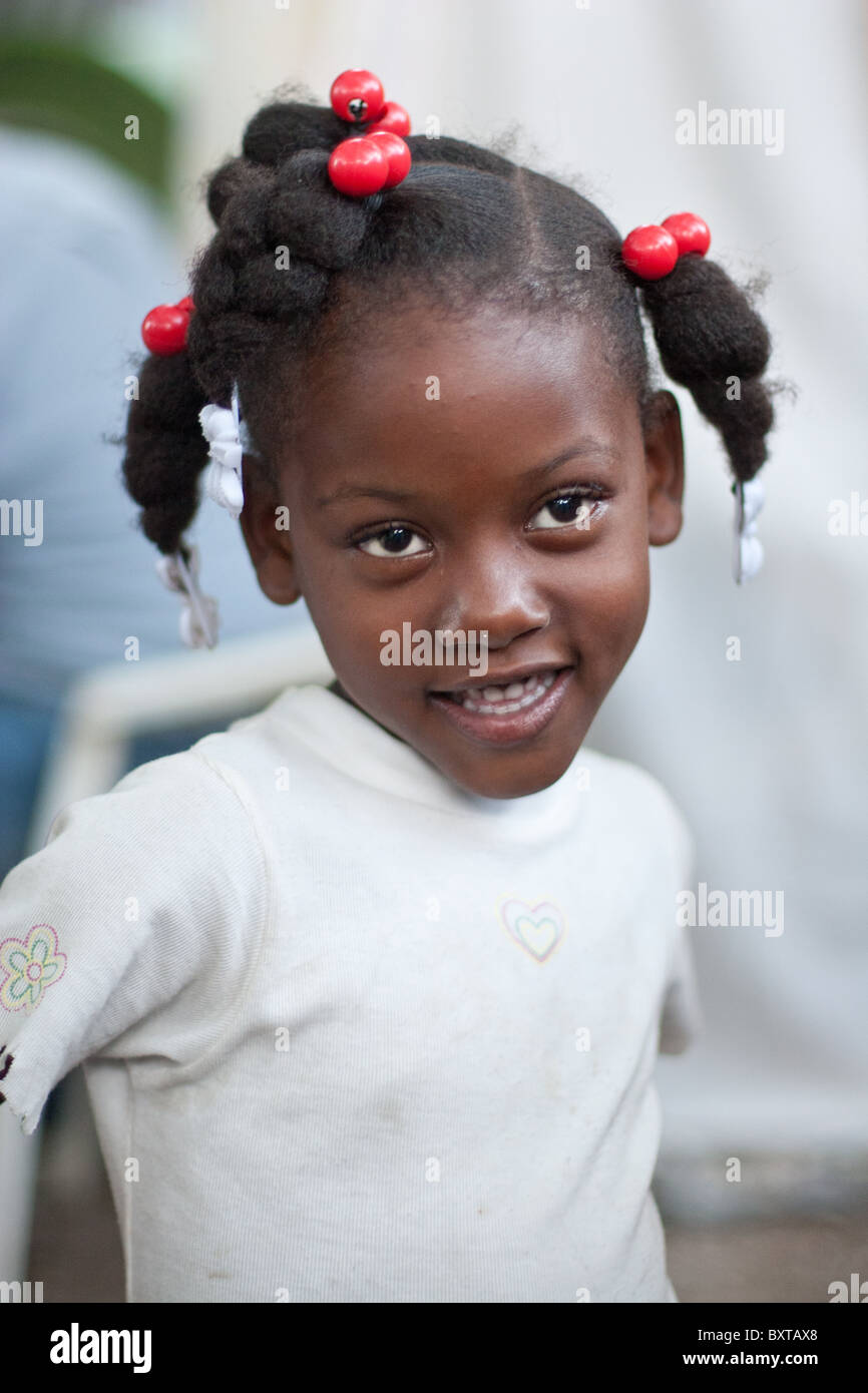 A Haitian child living a temporary camp waiting for food assistance from a humanitarian aid agency. - Stock Image