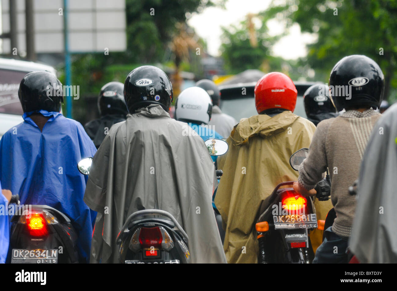 Motorcyclists in tropical rain Stock Photo