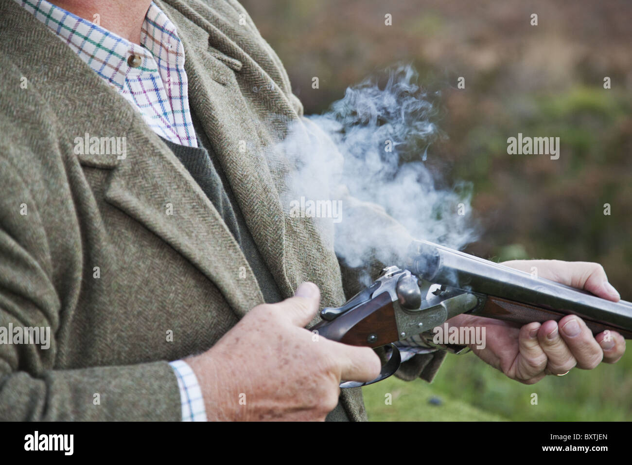 Detail photograph of well dressed man holding a shotgun during a pheasant shoot. - Stock Image