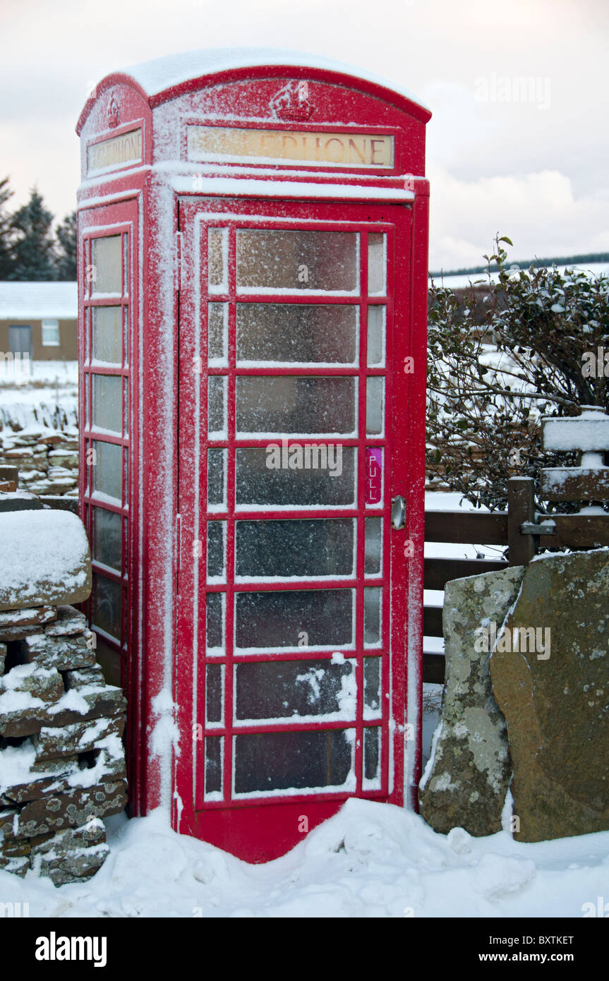 Type K6 British Telecom (BT) telephone box, snow covered, in the village of Mey, Caithness, Scotland, UK - Stock Image