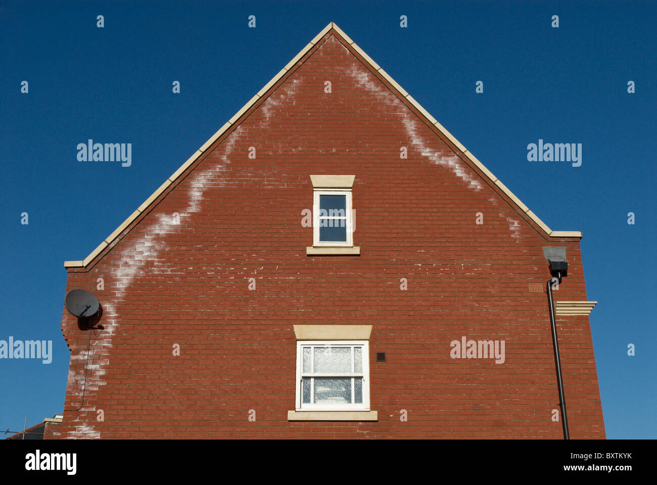 Brick wall of house showing signs of damp UK - Stock Image