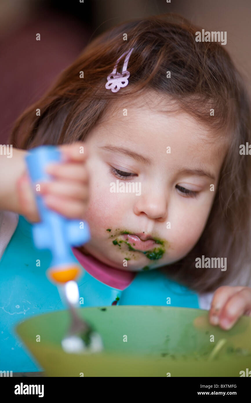 18 month old girl eating from a bowl - Stock Image