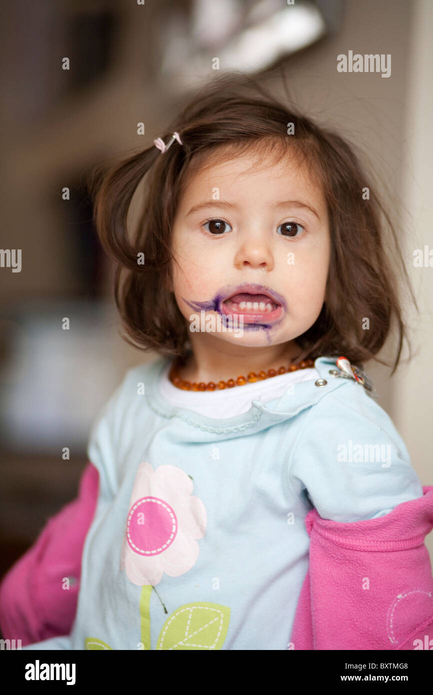 18 month old girl with coloured felt tip on face - Stock Image