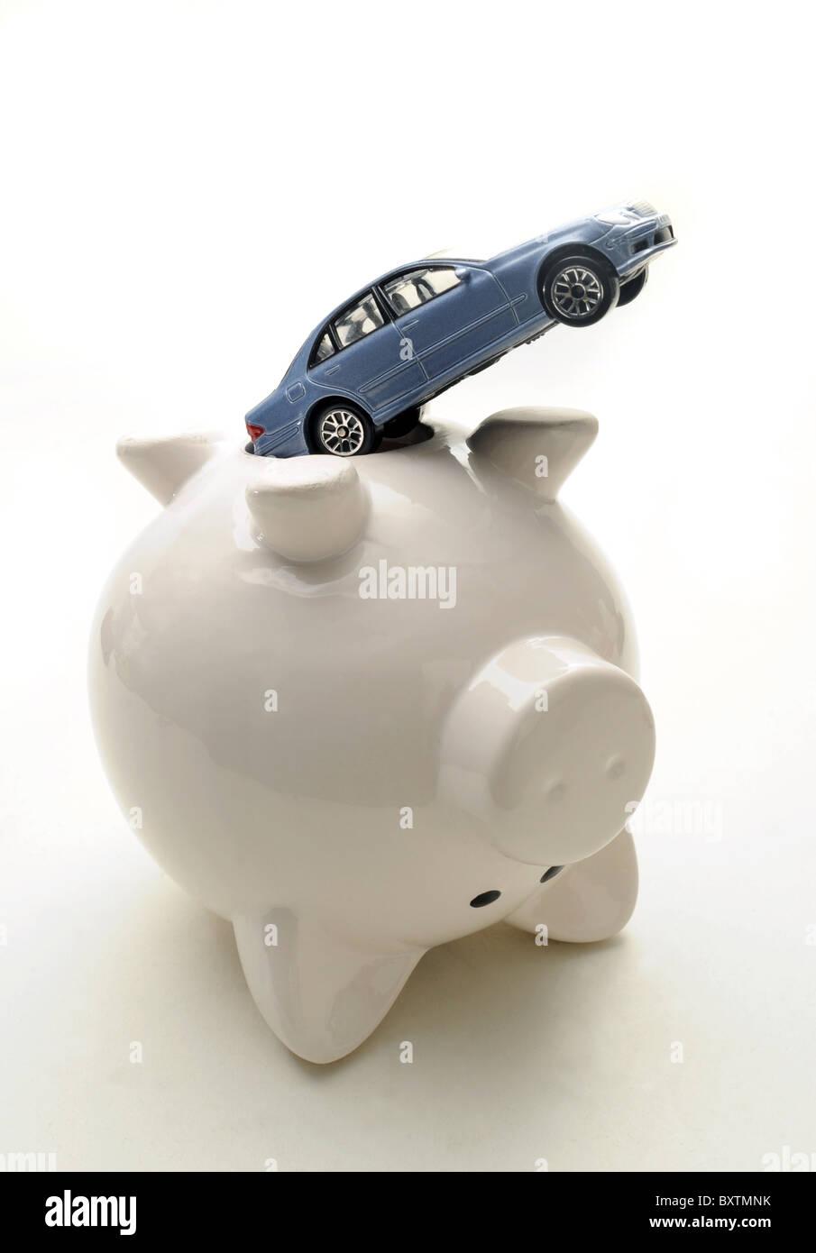 UPTURNED PIGGY BANK WITH CAR RE MOTORING RUNNING REPAIR COSTS BILLS  FUEL  INSURANCE PRICES GARAGE ETC UK - Stock Image