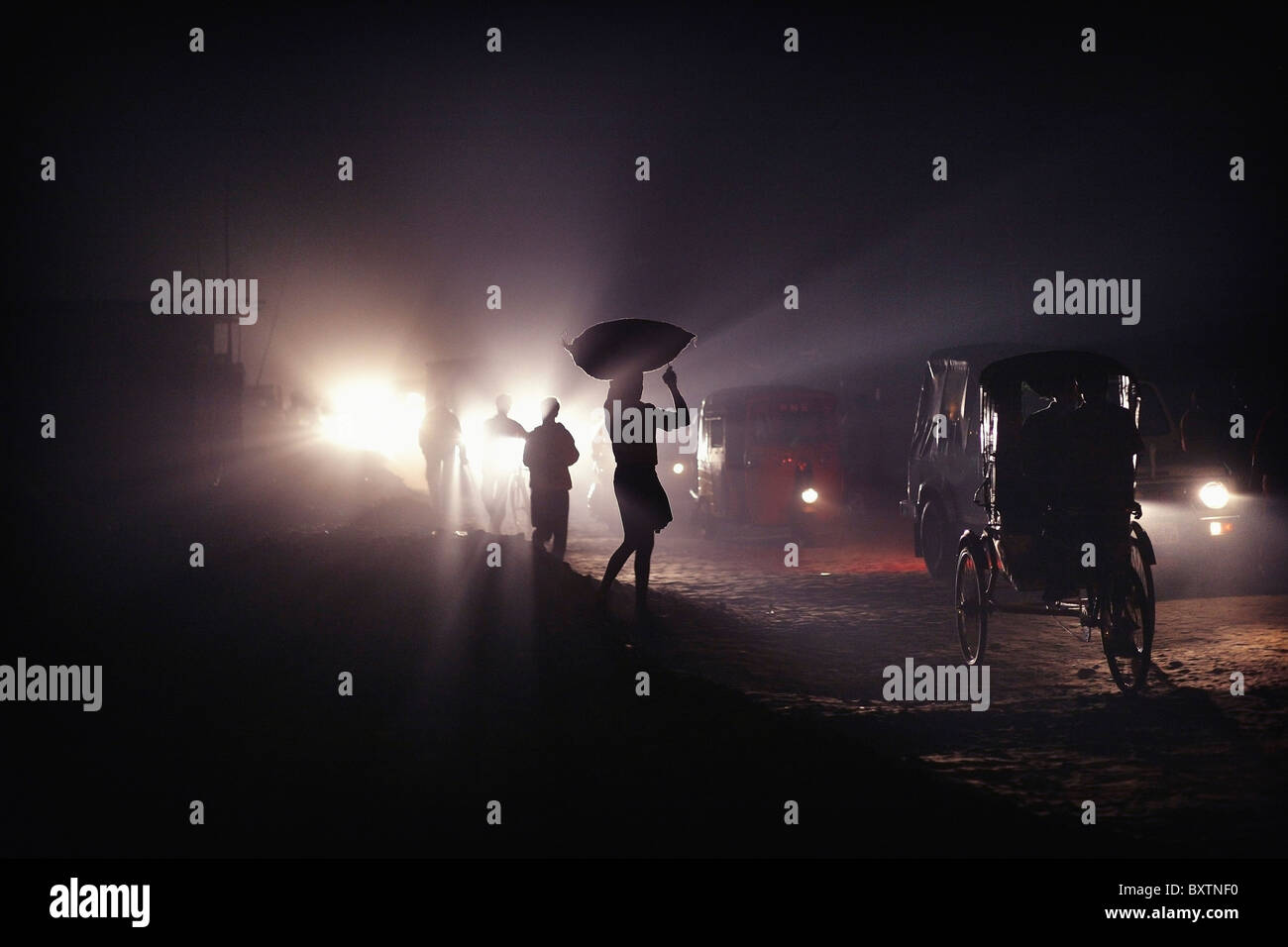 Silhouettes Of Traffic And People Carrying Sacks On Their Heads At Night - Stock Image