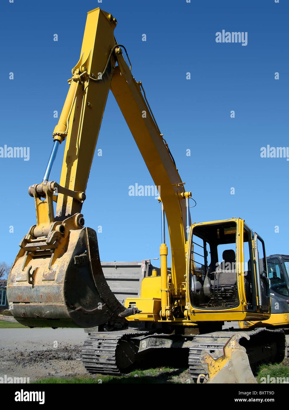 Vertical of mechanical digger in real street urban job site setting contrasted by bright blue sky. - Stock Image