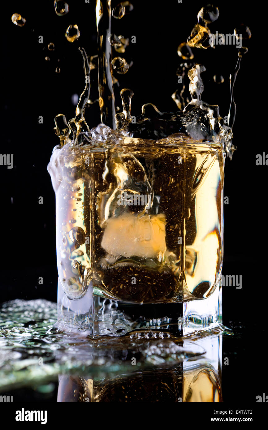 Glass of whiskey on a black background. Whiskey splash in a glass. Whiskey with ice. Stock Photo