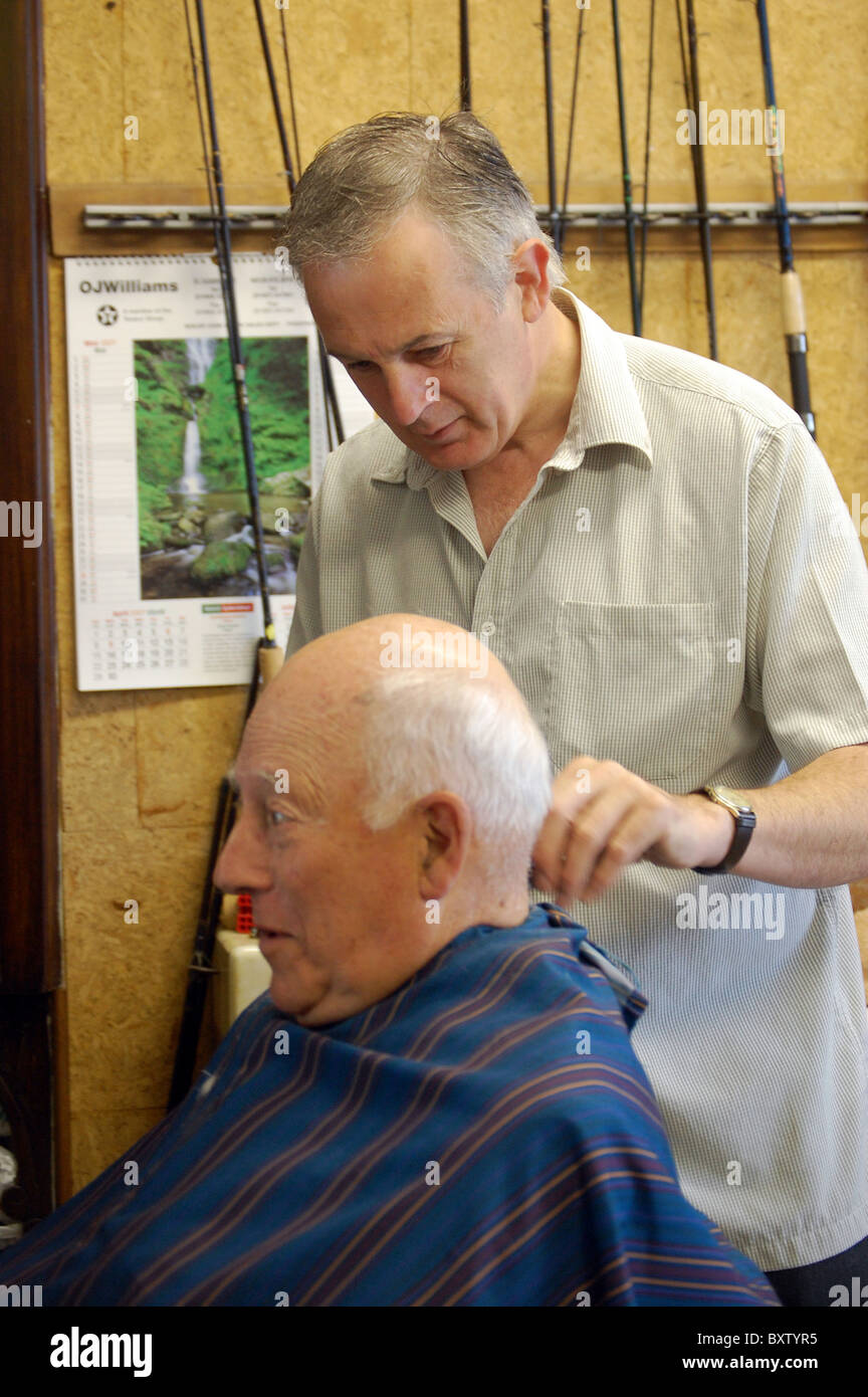 a old man has his hair cut in the barbers wish also sells