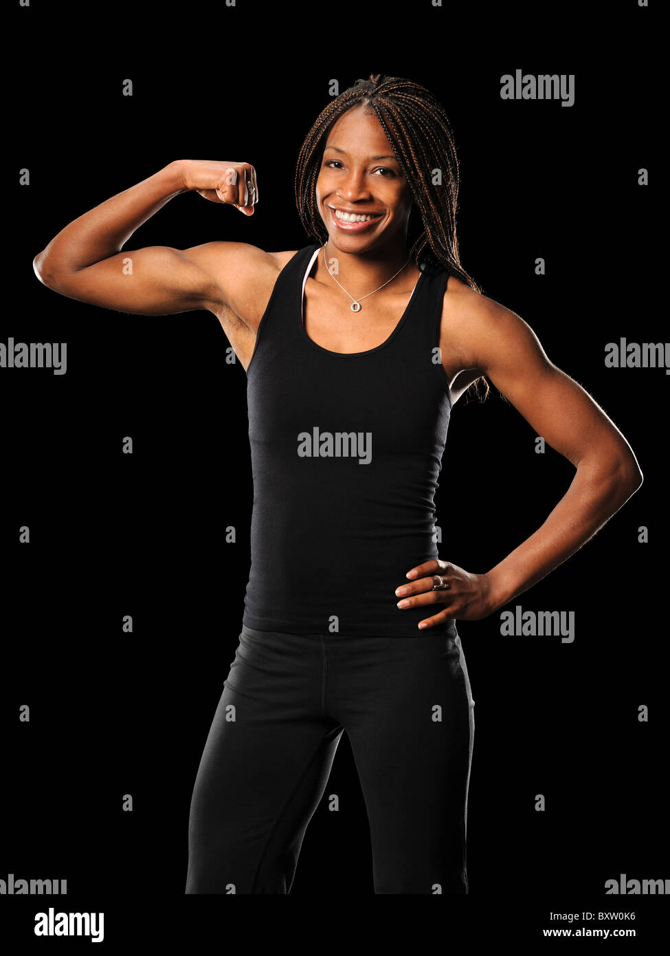 Young African American woman flexing biceps isolated over black background - Stock Image