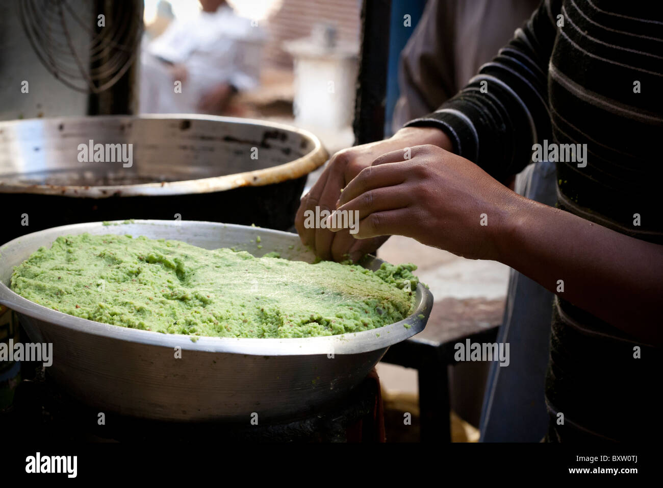 Close up of the hands of a falafel maker in a local street market, Luxor, Egypt, Africa - Stock Image